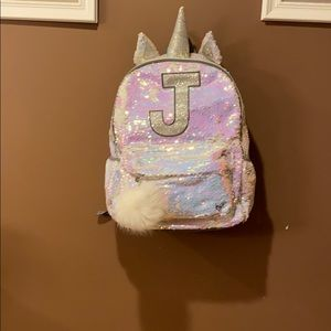 Girls unicorn backpack with letter J on it.